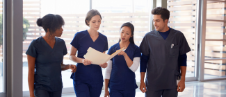 Three females and one male dressed in dark blue scrubs discussing a file